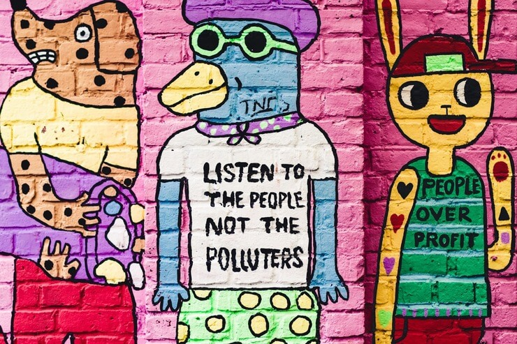 Colorful mural depicting a dog, a bird, and a rabbit dressed as humans. The dog is throwing out trash. The bird's t-shirt says 'Listen to the people, not the polluters'. The rabbit's t-shirt says 'People Over Profit.'